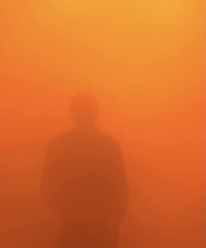 A person, barely visible, walking through the orange and yellow mist of the narrow hallway.