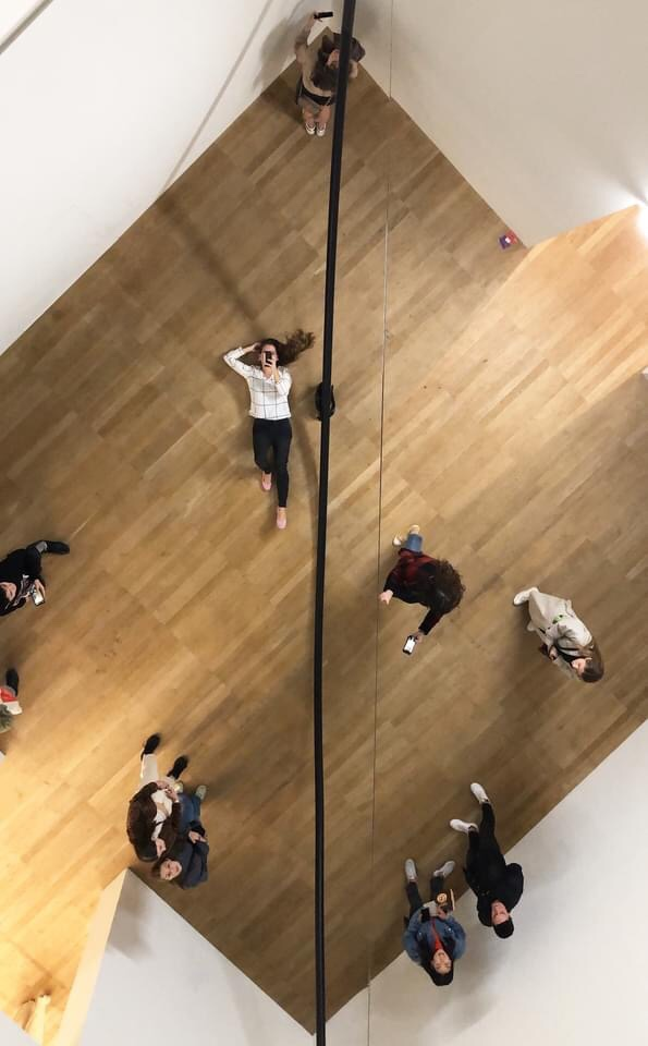 View looking up at my own reflection in a giant mirror installed on the ceiling.