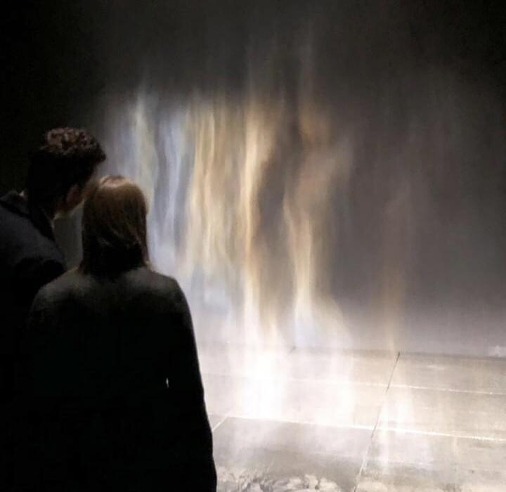 Two people observe the rainbow mist.