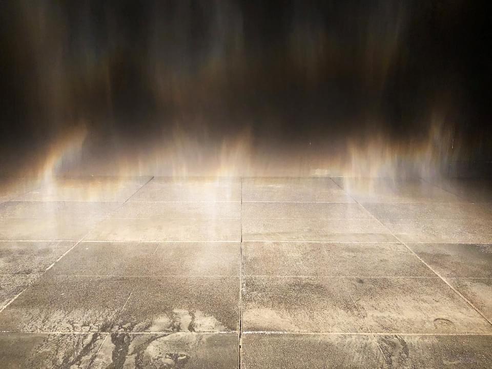 Rainbow mist against a dark wall.