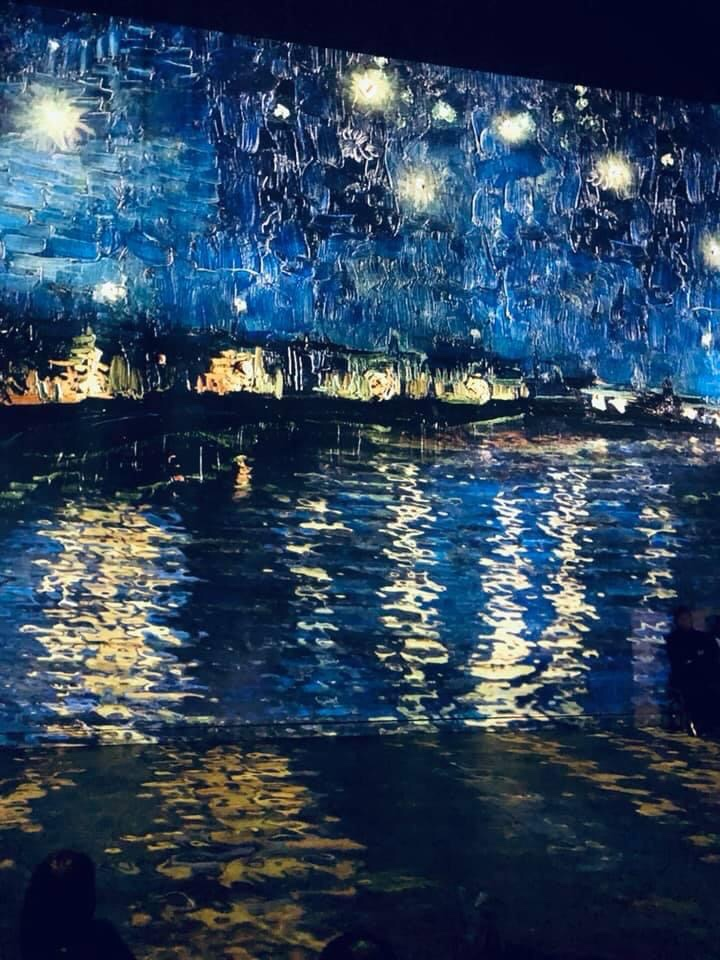 Blue and yellow dabs of paint depicting the impression of stars shining over a river in France.