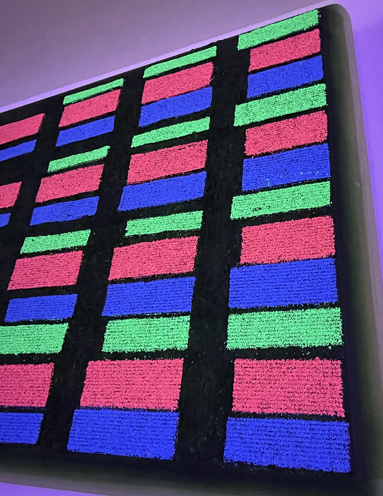 Close-up of patterned blocks in red, green and blue, which appear flourescent and glowing on the panel.